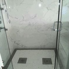 Marble look porcelain walls & complementary mosaic floor give this shower a luxurious vibe (Photo/Installation: Celebre Tile) #tilestyle #tileaddiction #porcelain #marble #walls #mosaics #showers #floors #bathrooms #tiles #installation #commercial #residential #design #getinspired #gettiled #CelebreTile #tileprofessionals #21royalcrestrd #etobicoke