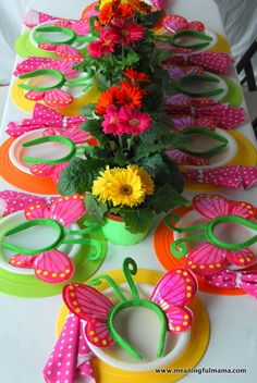Layers of paper circles in bright colours (with maybe a flat butterfly design on one) under bright plates with bright serviettes & flowers
