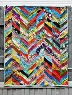 We love this scrappy rainbow chevron quilt! Put it on a bed or use it as a picnic blanket. whatever the case, you'll get your fabric stash to a manageable level AND a fresh new quilt out of the deal! Colchas Quilt, Scrappy Quilts, Baby Quilts, Quilt Blocks, Jaybird Quilts, Quilt Binding, Quilt Top, Quilting Tutorials, Quilting Projects