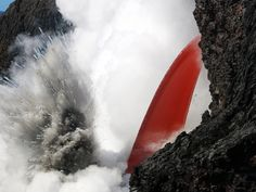 An open lava stream pours out of the lava tube, perched high on the sea cliff, and into the ocean.