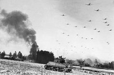 Low flying C-47 transport planes roar overhead as they carry supplies to the besieged American Forces battling the Germans at Bastogne, during the enemy breakthrough on January 6, 1945 in Belgium. In the distance, smoke rises from wrecked German equipment, while in the foreground, American tanks move up to support the infantry in the fighting.