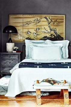 Asian-inspired bedroom with moody colors and dark bedside table