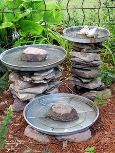 Stacked stone bird baths with galvanized trash can lid saucers