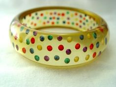 Bakelite Bangle. Once upon a time, this chunky transparent Bakelite bangle with Shultz reverse carved and multi colored painted polka dots was ice blue