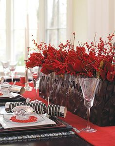 Vibrant Holiday Tabletop    Set the table in style with a scarlet scheme that's rich and festive yet modern.    Table settings are layered on a red velvet and organza runner with accents like red-glass pebbles, beaded napkin rings and oversize faux diamonds to lend sparkle. A long, low centerpiece of bold ruby amaryllis and ilex berries reinforces the holiday palette.