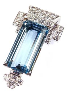 An Art Deco aquamarine and diamond cluster clip brooch by Cartier, London circa 1935. Set with a principal step-cut rectangular aquamarine, to one end a stepped design of square cut diamonds and flared scroll pavé set with round brilliants, to the other end a trefoil diamond cluster. Length 4.3cm. #Cartier #ArtDeco #clip