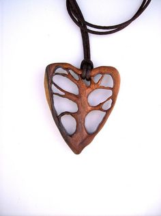 This light weight pendant is hand carved in East Indian Rosewood. With its stylish heart-shaped contour surrounding the Tree of Life, this fashion forward pendant would always set you apart from the crowd. - The color of the wood looks different in natural light versus artificial light, making it even more interesting and versatile.    - The pendant measures approximately 2 tall by 1.6 wide ( 5cm by 4.2cm).    - The pendant comes with a 29 (74cm) brown satin cord that you can tie as long or…