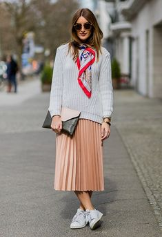 Sofia Grau wearing a pleated midi skirt, grey jumper and adidas Stan Smith trainers