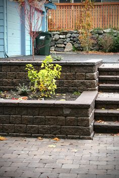 tiered step down retaining wall for sloped yards. Vegetable garden in bottom. Railing on right side.