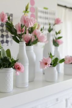 Verschillende witte vaasjes met bloemen.