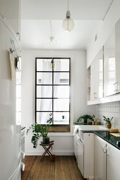 White galley kitchen with long black window
