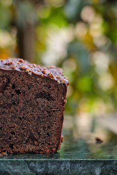 Ingrédients: Pour le cake - 200 g de beurre à température ambiante + 1 peu pour le moule - 120 g de sucre - 4 oeufs - 1/2 sachet de levure - 180 g de farine + 1 peu pour le moule - 45 g de poudre d'amande - 30 g de cacao en poudre non sucré - 150 g + 75 g de chocolat noir - 1 pincée de fleur de sel Pour le glaçage rocher - 200 g de chocolat noir - 40 g d'huile de tournesol ou de pépin de raisin - 50 g de noisettes