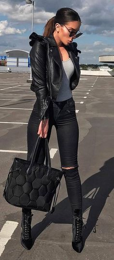 trendy black outfit idea : leather jacket + bag + heels + rips + grey top
