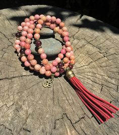 This premium 108 crystal bead mala is made of RHODONITE & GARNET beads and is accented with bronze-tone spacers which are lead-free, iron-free. Length: 36. The 3 suede tassel is shown in RED, but may be customized to any other color of your liking.     | Crystal Healing Gemstone Mala Beads for Meditation, Mantra, Mudra, Pranayama & Yoga Jewelry by Mayan Rose MayanRoseShop on Etsy |