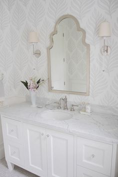 Mirror is from Layla Grace. Sconces: Circa lighting – Camille Long Sconce- Polished nickel –  Marble Herringbone Floor Tile: Olympia tile –Statuario marble countertop
