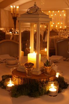 Wooden slice table centre with moss, succulents, votives and a vintage-style lantern by www.stressfreehire.com #venuetransformers