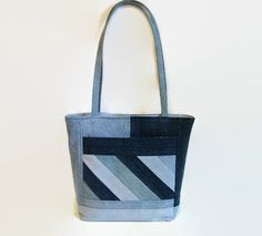 This large denim blue jean tote bag, handbag, shoulder bag or purse was constructed from a variety and shades of upcycled recycled denim blue jeans and repurposed cotton fabric. This tote bag is spacious and durable, a perfect size to comfortably carry your daily must have items, magazines, books and miscellaneous items. The unique exterior front and back was constructed from a variety of upcycled light and dark denim blue jeans. There are two 10 x 7 3/4 exterior pockets, one on each side of…