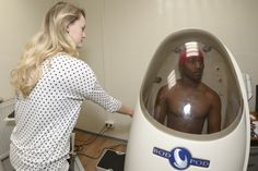 Valerie Greene, a health educator at Stuttgart Army Health Clinic's Wellness Center, conducts a Bod Pod body composition test on Spc. Shawn Murphy, from the Physical Therapy Department at Stuttgart, Feb. 2. The Bod Pod is the latest addition to the Wellness Center's array of tools used to enhance healthy living in the community. U.S. Army photo by Kevin S. Abel.