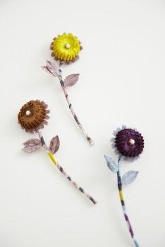"""色彩豊かな花たちが楽しげにおしゃべりしているように咲いている様子が木彫りされたような素朴な表情で描かれたテキスタイル""""hanna""""。茎部分に用いたテキスタイルがカラフルに、活き活きとした花の表情を幾重にも重ねた花びらで表現しています。冬のコーディネートに優しいニュアンスを添えてくれそうです。(2013a/w) http://www.mina-perhonen.jp/metsa/RA/7118/"""