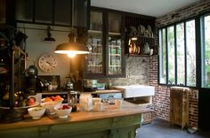 pendant lamp in kitchen, farmhouse sink, rustic tables, exposed brick, glass door cabinets