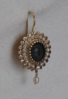 """18 Kt yellow gold earrings in Sardinian filigree. Each earring has an oval black intaglio onyx, is surrounded by """"scaramazza"""" pearls and accented by a diamond. Hand made by Davide Masia."""