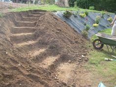 Salut, Après quelques jours sans nouvelles, nous revoilà pour de nouvelles aventures: Réalisation d'un escalier entre la plateforme et les hauteurs du jardin. Je commence par former les marches à la pelle et à la pioche dans le talus. Ensuite, je creuse...