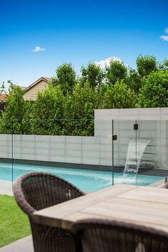 piscina con fuente cascada y valla de vidrio