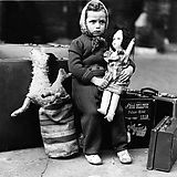 London Blitz: An unhappy little girl is waiting at the train station with her luggage to be evacuated to the British countryside. One in six Londoners were rendered homeless by the Blitz.