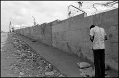 Larry Towell. GAZA STRIP. Khan Younis Camp. October 2003. A Palestinian man prays beside the wall separating the Jewish Gush Katif settlement from the Khan Younis refugee camp. He awaits permission to return to his village of El-Moasy, which is surrounded by the illegal Gush Katif settlement. To return home he must pass through an Israeli military checkpoint.