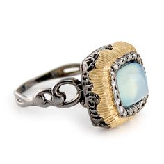 Cabochon Blue Sapphire Ring 14kt yellow and white gold ring with black rhodium, a squared cabochon blue sapphire in center surrounded by .20ctw round brilliant diamonds