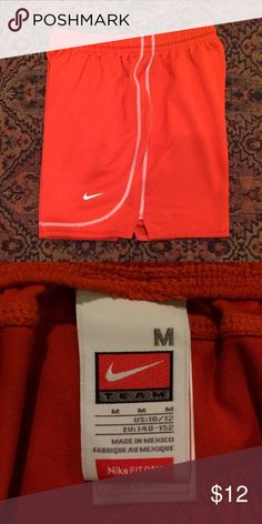 Nike Shorts Women's Dri Fit Nike shorts in orange with a white seam and Nike check. These have a black drawstring on the inside to loosen or tighten. About an inch longer than regular Nike tempo shorts. Nike Shorts