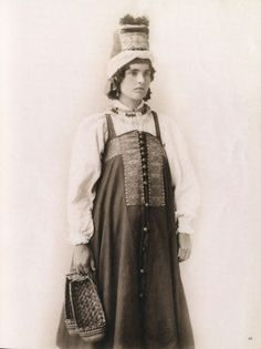 woman in traditional Russian costume holds lapti in her hand - kind of village shoes