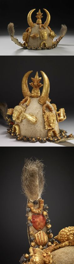 Africa | A ceremonial helmet (denkyemkye) made of antelope hide with a scalloped fringe and long cheek straps situated on either side. The straps have additional pieces of hide attached to the ends which have long tufts of antelope fur sewn to them. The helmet, flaps and fringe have twenty ornaments added to their exterior surfaces arranged symmetrically in groups. All have wood cores which are plated with sheet gold | Royal Palace, Kumase, Asante region, Ghana | 19th century   ||  {9.4}