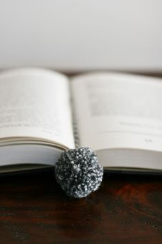 DIY Pompom Bookmark Tutorial from Design Mom here.Use up your yarn to make really cheap and cute gifts or stocking stuffers. http://www.designmom.com/2012/10/the-perfect-gift-yarn-ball-bookmark/