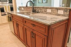 Fabuwood Cabinetry, Wellington Spice kitchen island, two tone kitchen cabinets, two tone granite, beautiful Wainscot panel on the end of the kitchen island.