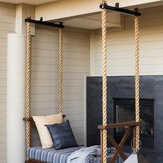 Covered Patio with Rope Swinging Bed in Front of Fireplace