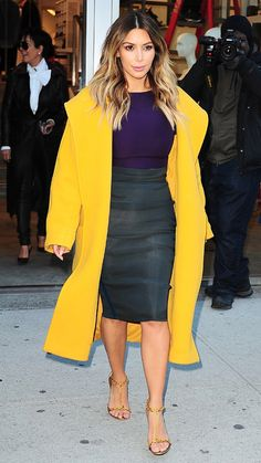 While in New York City, Kardashian added some pops of color to her usually neutral wardrobe by pairing a black pencil skirt with a purple top and bright yellow coat. She finished the outfit with one of her favorite pairs of gold sandals.