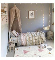 Une chambre enfant avec un mur gris et un ciel de lit rose