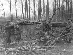 German POWs carrying wounded Private Johnson of the 407th Reg/104th Infantry, 23 Feb 1945