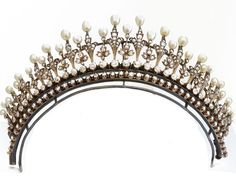 A French tiara, 1880, with multiple fleur de lys mofits and floral spacers, all topped with pearls, and rising from a double band of diamonds.
