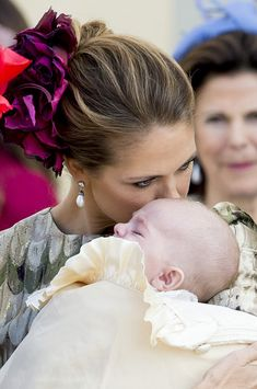 The four-month-old slept through much of the baptism but did make himself heard after the service.  Princess Madeleine plants a kiss on the head of Prince Nicolas.