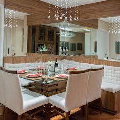 Sala de jantar com lustre e espelho de Raduan Arquitetura