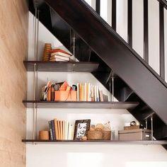 Les étagères suspendues sous l'escalier la meilleure façon d'utiliser l'espace sans le charger. Comme un prolongement des marches, les étagères sont accrochées par de fins câbles en acier pour un côté aérien.