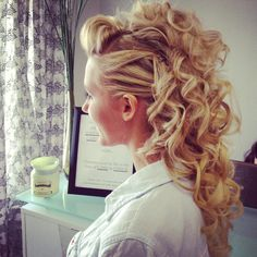 Formal style designed by adding extensions and curling hair into a long ponytail with a teased faux hawk section in front