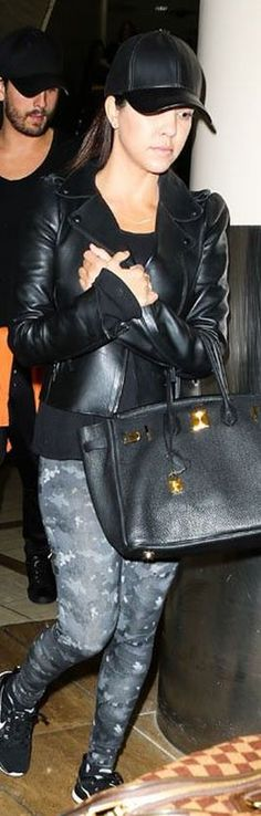 Who made  Kourtney Kardashian's black leather jacket, tote handbag, and sneakers?