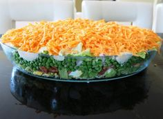 The Seven Layer Salad is a make ahead retro dish from the 70's that is a full meal in a bowl: lettuce, peas, onion, bacon, eggs, mayo and cheese.