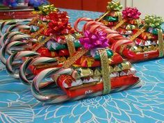 "Christmas Candy Sleighs  First you glue a kitkat bar to two candy canes to create the base.  Next, attach 10 mini hershey bars on top, with just a drop of glue for each. You stack them in a pyramid.  After all the glue is hard and secure, glue ribbon around your ""packages"" and a bow on the top.  https://scontent-b-ord.xx.fbcdn.net/hphotos-prn2/1383526_714816038546524_260584801_n.jpg"