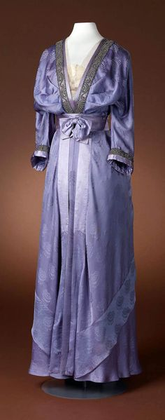 Dress, Hirsch & Cie, ca. 1910-15. Three-piece purple or lilac gown with long-sleeved bodice, deep V-neck, belt, and skirt. Belt or waistband is pleated and has bow. Amsterdam Museum