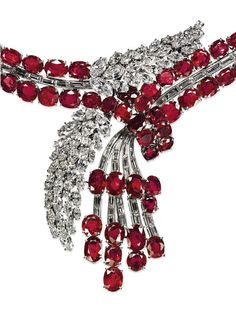 A SUPERB RUBY AND DIAMOND NECKLACE Of cascade design, the front set with a baguette-cut diamond tassel with oval-shaped ruby terminals together with a marquise-cut diamond asymmetric double foliate motif, to the twin oval-shaped ruby and baguette-cut diamond neckchain, 1950s, 39.0 inner circumference, with French assay mark for platinum and gold.