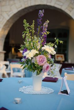 Centerpiece featuring blue bird roses and delphinium in vintage milk glass.